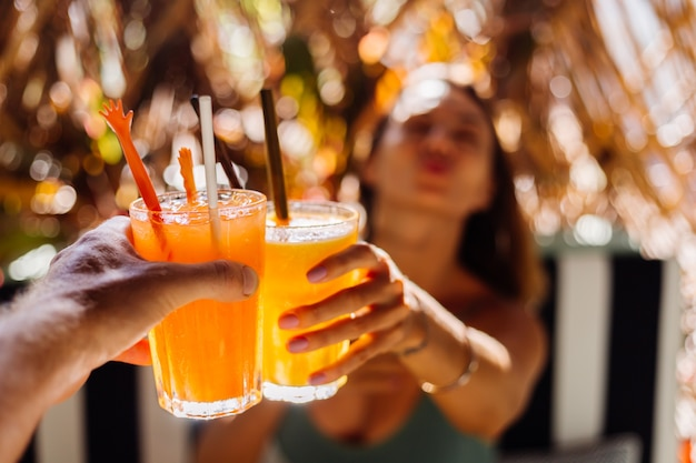 Pareja de amigos tintineo de vasos de sabrosos cócteles tropicales en un día soleado en la cafetería