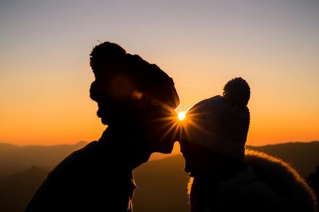 Pareja en amor silueta de luz de fondo en la colina en el momento de la puesta del sol