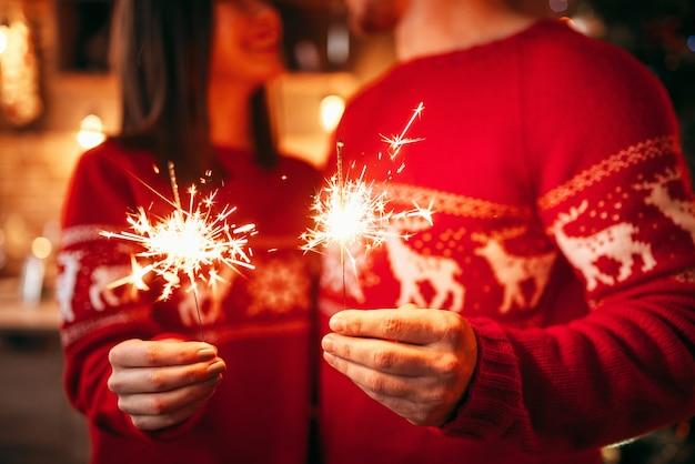 Pareja de amor tiene luces de bengala en las manos, celebración romántica de navidad. hombre y mujer celebran la navidad juntos