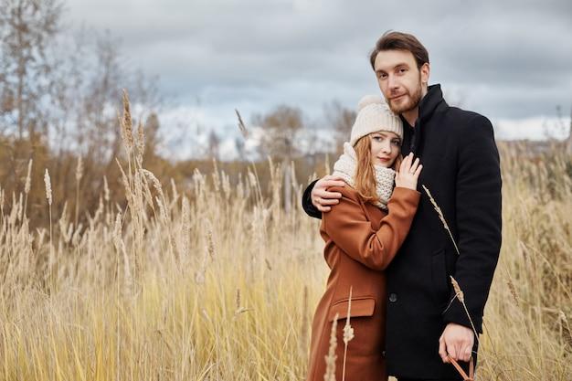 Pareja amorosa abrazando en campo, paisaje de otoño