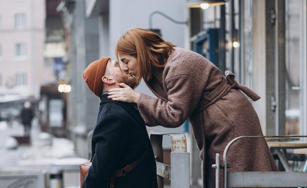 Pareja amorosa adulta besándose en una calle