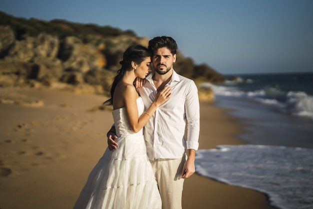 Pareja amorosa caucásica vistiendo ropa blanca y abrazándose en la playa durante una sesión de fotos de boda