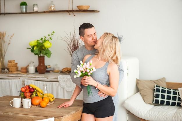 Pareja amorosa en una cocina rústica y espacio de copia. pareja amorosa con tatuajes en una cocina de estilo escandinavo.