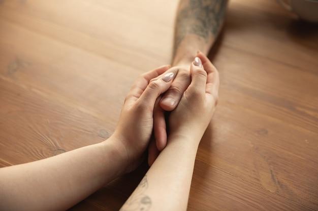 Pareja amorosa cogidos de la mano de cerca en el escritorio de madera