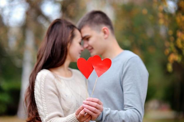 Pareja amorosa con corazón rojo en el parque otoño. concepto de amor de citas de san valentín