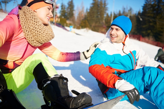 Pareja amorosa divirtiéndose tanto esquiando