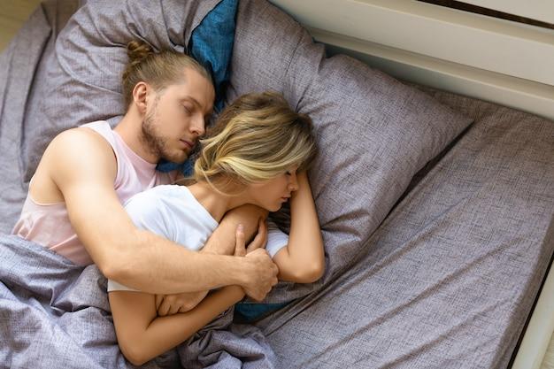 Una pareja amorosa está durmiendo en la cama, el esposo abraza a su esposa desde la recuperación de la espalda y el sueño saludable c ...