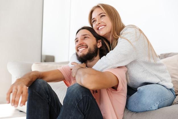 Una pareja amorosa joven positiva en el sofá ve la película de televisión en el interior de su casa mirando a un lado.