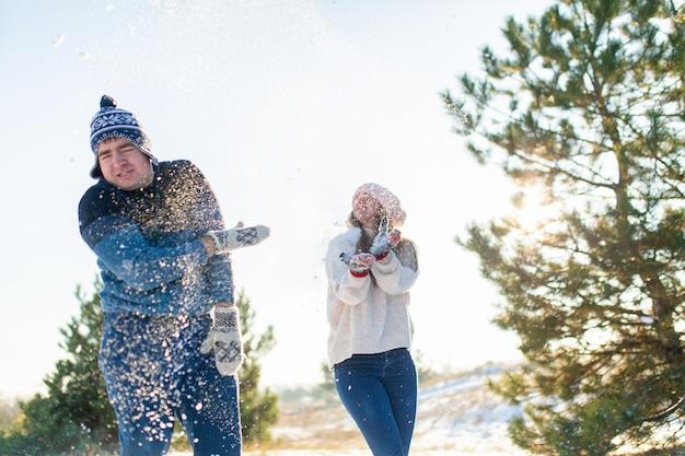 Pareja amorosa jugar bolas de nieve en invierno en el bosque