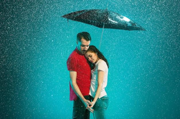 La pareja amorosa bajo la lluvia con paraguas sobre un fondo turquesa