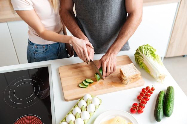 Pareja amorosa de pie en la cocina y cocinar juntos