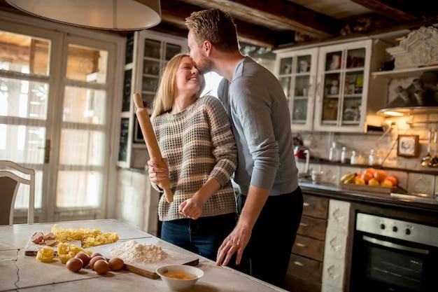 Pareja amorosa preparando pasta en la cocina