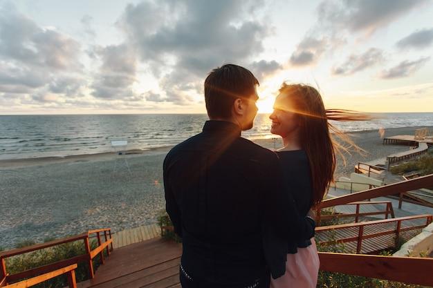 Pareja amorosa en la primera cita conoce la puesta de sol en el mar