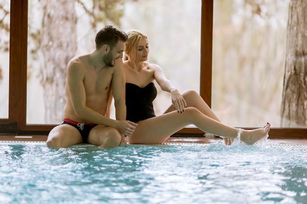 Pareja amorosa que se relaja en el spa junto a la piscina.