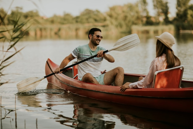 Pareja amorosa remando en el lago
