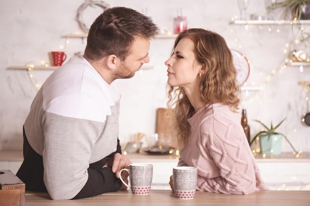 Pareja amorosa en ropa de invierno en la cocina