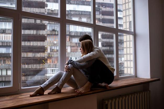Pareja amorosa sentados juntos y mirar por la ventana