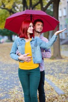 Pareja amorosa bajo una sombrilla en el parque de otoño