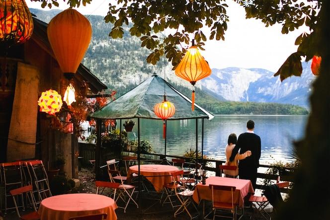 Pareja amorosa toma una hermosa tarde con linternas cerca del lago