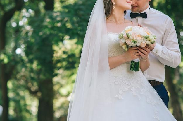 Pareja amorosa tomados de la mano con anillos contra el vestido de novia