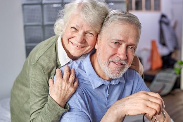 Pareja de ancianos de los 60 relajándose en casa, posando sonriente momento de captura para la sesión de fotos del álbum familiar en el interior, abuelos canosos amor eterno