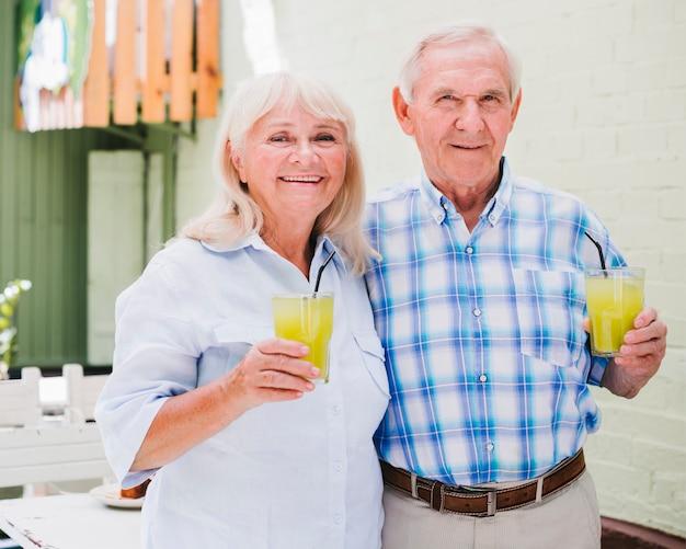 Pareja de ancianos abrazados sosteniendo vasos de jugo