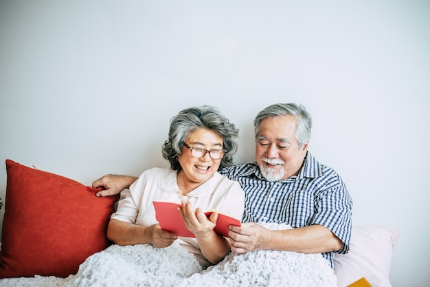 Pareja de ancianos acostada en la cama y leyendo un libro
