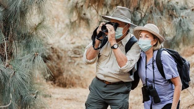 Pareja de ancianos activa disfrutando de la belleza de la naturaleza durante la pandemia de covid-19