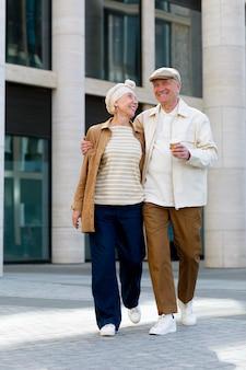 Pareja de ancianos al aire libre en la ciudad con una taza de café