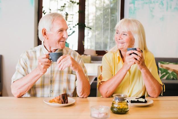 Pareja de ancianos alegre bebiendo té y hablando animadamente