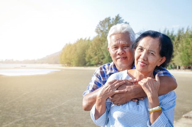 Pareja de ancianos asiáticos abrazándose junto al mar