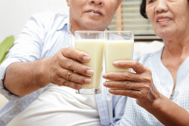 Pareja de ancianos asiáticos bebe leche rica en calcio para prevenir la osteoporosis.