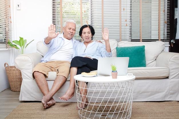Una pareja de ancianos asiáticos sentados en la sala de estar levanta la mano para saludar a los hijos y nietos a través de un video en línea en el portátil. copia espacio