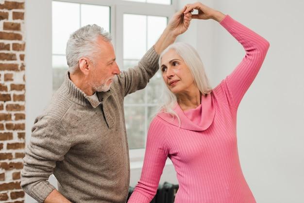Pareja de ancianos bailando en casa