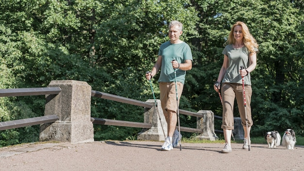 Pareja de ancianos con bastones de trekking tiro largo