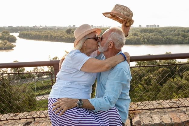 Pareja de ancianos besándose fuera de tiro medio