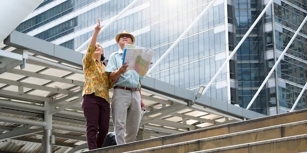 Una pareja de ancianos camina, arrastra su equipaje y sostiene un mapa para navegar por las calles.