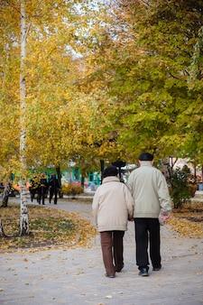 Pareja de ancianos caminando en el parque otoño