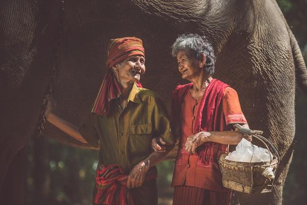 Pareja de ancianos caminando con su elefante en la selva, en tailandia