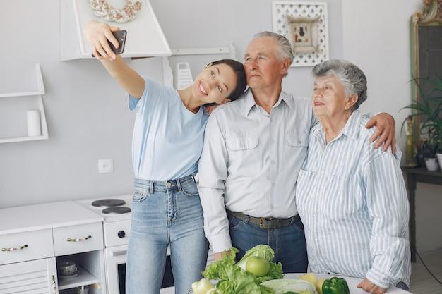 Pareja de ancianos en una cocina con joven nieta