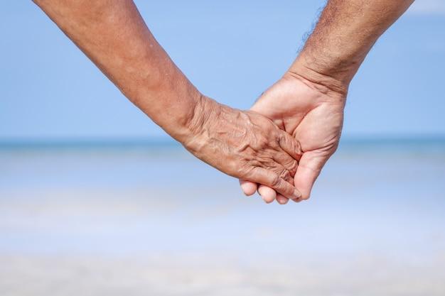 Pareja de ancianos cogidos de la mano para viajar al mar cuídate