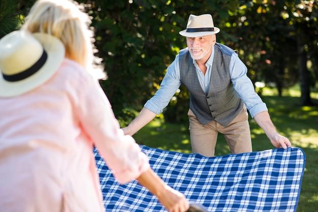Pareja de ancianos colocando una manta sobre la hierba