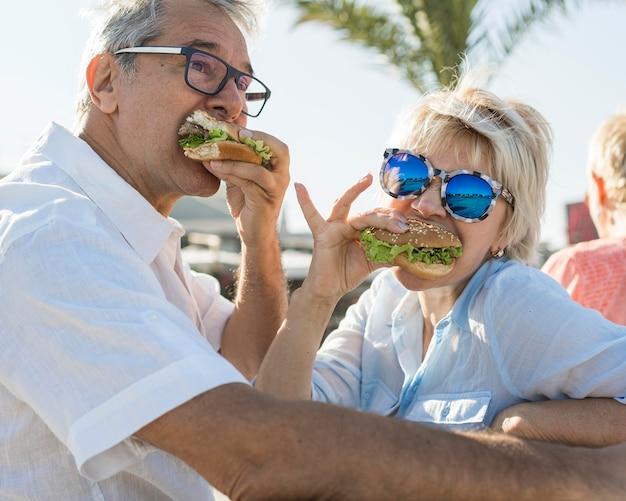 Pareja de ancianos comiendo una hamburguesa al aire libre
