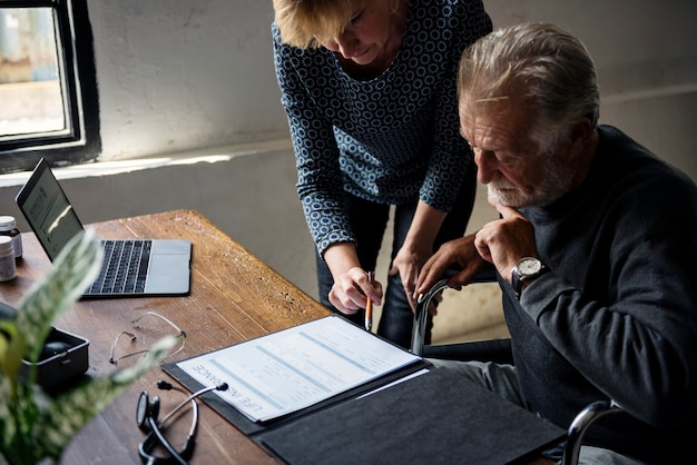Pareja de ancianos completando un formulario