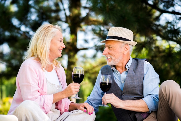 Pareja de ancianos con copas de vino en la naturaleza