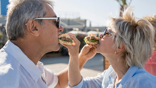 Pareja de ancianos disfrutando de comer una hamburguesa al aire libre