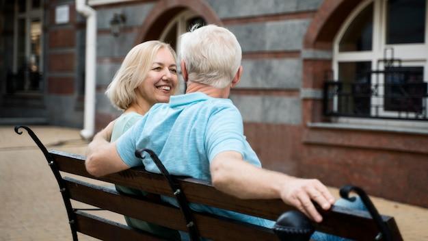 Pareja de ancianos disfrutando de su tiempo en un banco al aire libre