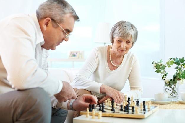 Pareja de ancianos divirtiéndose con el ajedrez en casa