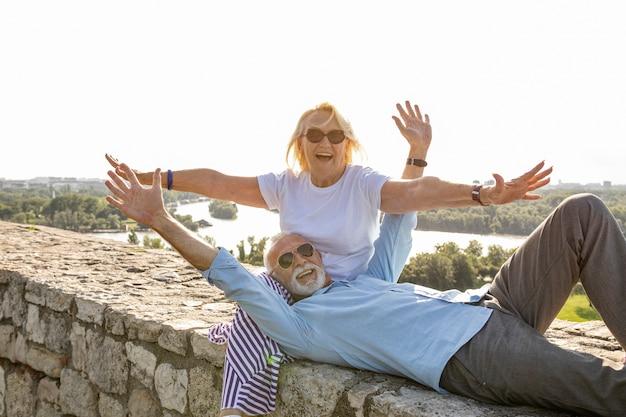 Pareja de ancianos estirando los brazos en el aire