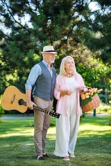 Pareja de ancianos con guitarra y cesta de picnic